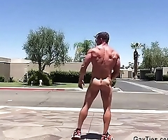 Muscleman strips naked on the street
